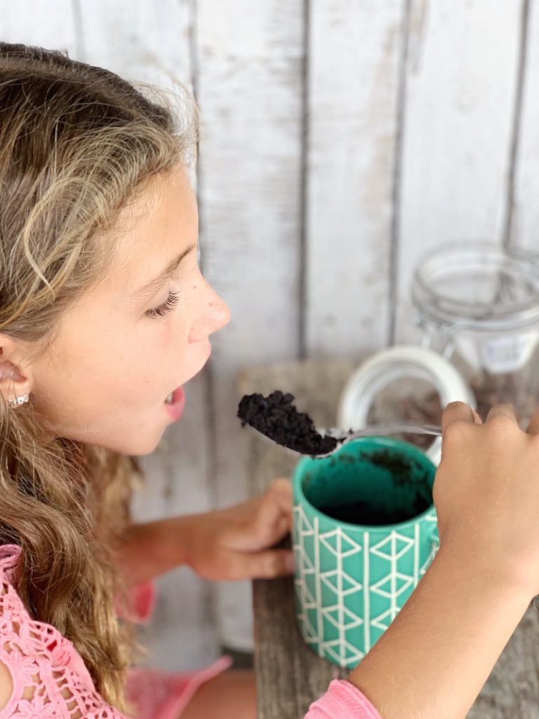 girl taking a bite of eggless chocolate cake out of a green mug