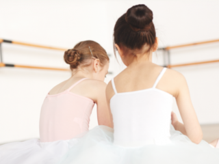 2 girls in dance outfits sitting in a dance room with buns