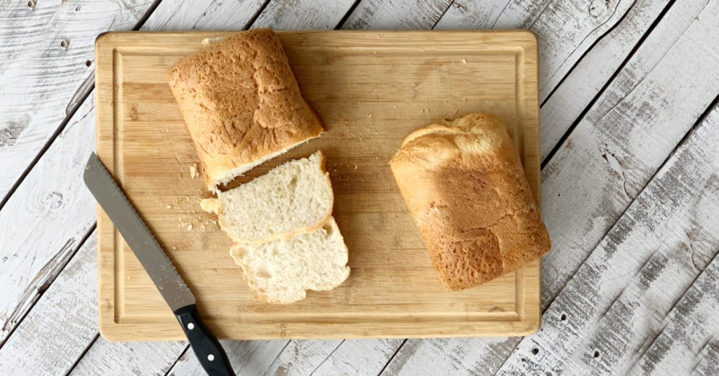 Overhead view of bread on a cutting with bread knife with a few slices cut.