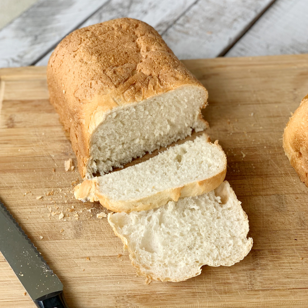 bread on a cutting with bread knife with a few slices cut.
