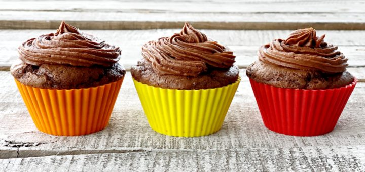 Three chocolate cupcakes lines up in a row with chocolate frosting.