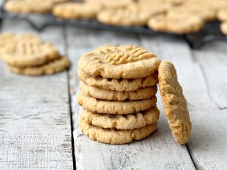 Stack of cookies with another cookie laying against stack