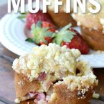 strawberry muffins cracked open in front of a white plate with strawberries with more muffins.
