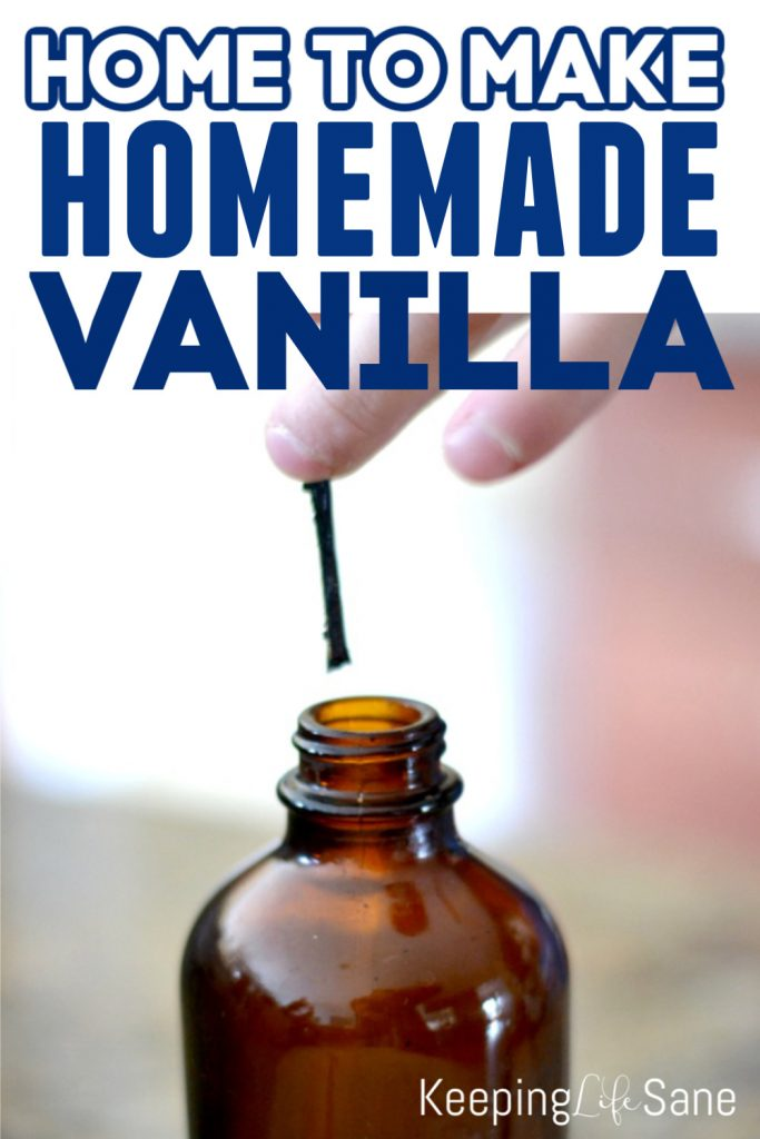 hand putting vanilla bean in brown bottle