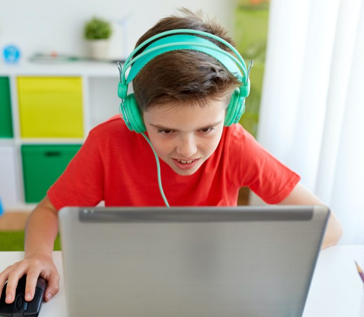 boy at desk with headphones working on computer
