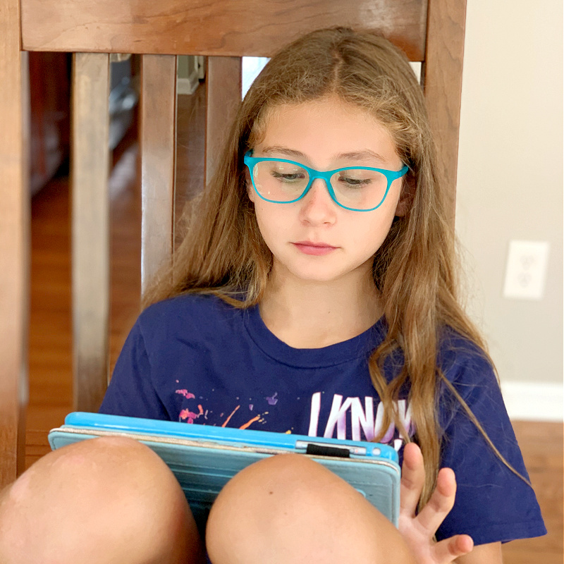 girl in glasses on iPad