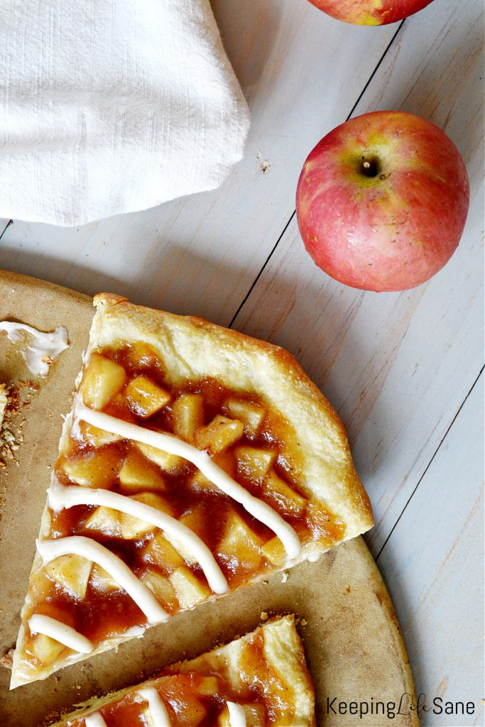 overhead view of slice of apple pie pizza with red apple
