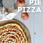 Overhead view of apple pie pizza with icing swirl with 2 red apples and pizza cutter