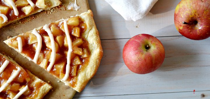 Slice of apple pie pizza with 2 red apples