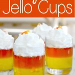 dessert cups with yellow and orange jellos with whiopped cream on top