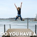 Kid in jeans jumping off dock into a lake.