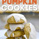 Stack of 4 pumpkin cookies with icing with one leaning against the stack