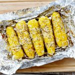corn on the cob with cheese on top on top of foil