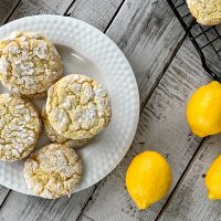 overhead view of white plate with lemon cookies with lemons on wooden table