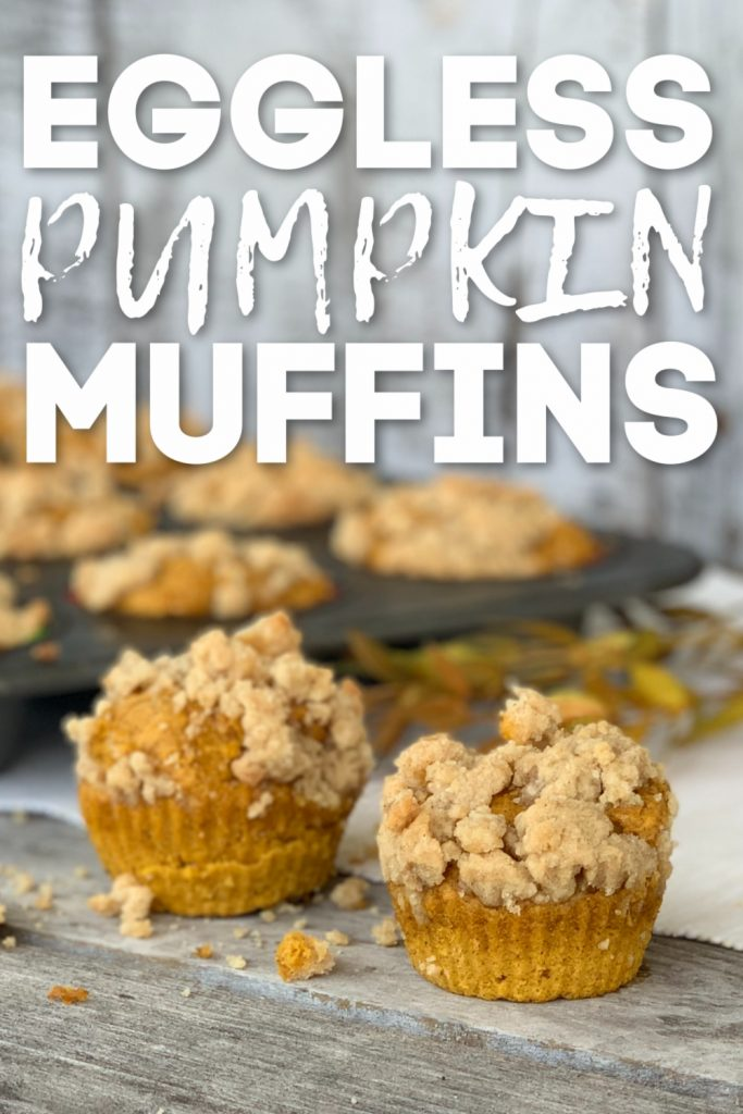 2 pumpkin muffins with crumbles on tiop with muffin tin in background