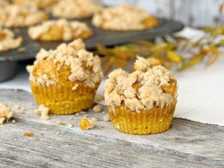 2 pumpkin muffins with muffin tin in background