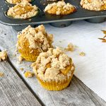 2 pumpkin muffins with crumbles on top with muffin pan in background