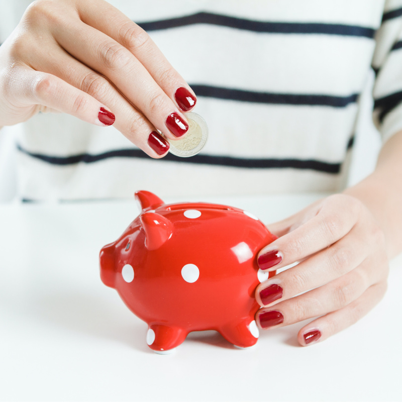 Lady with red fingernails adding a coin to a small red piggy bank.