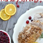 Cooked turkey breast on white plate with organe slices and cranberry sauce