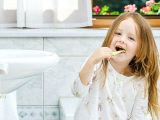 Little girl cleaning the teeth in bathroom, morning