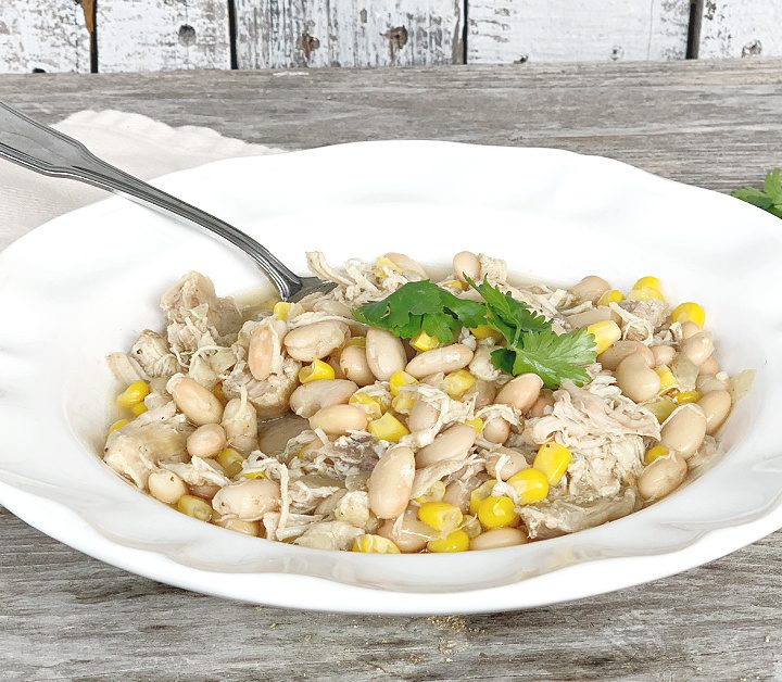 White Bowl of white chicken chili with napkin and cilantro