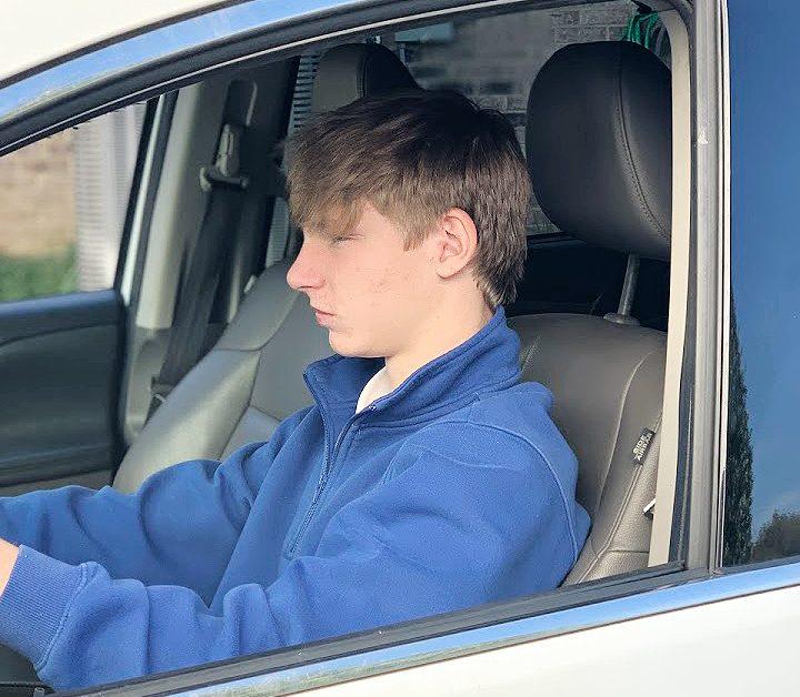 up close boy teen in blue sweatshirt driving white van
