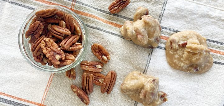 small bowl of pecans and pecan pralines on fall tablecloth
