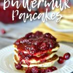 stake of pancakes with cranberry sauce on top