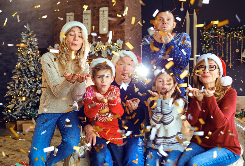 familu at Christmas time blowing confetti