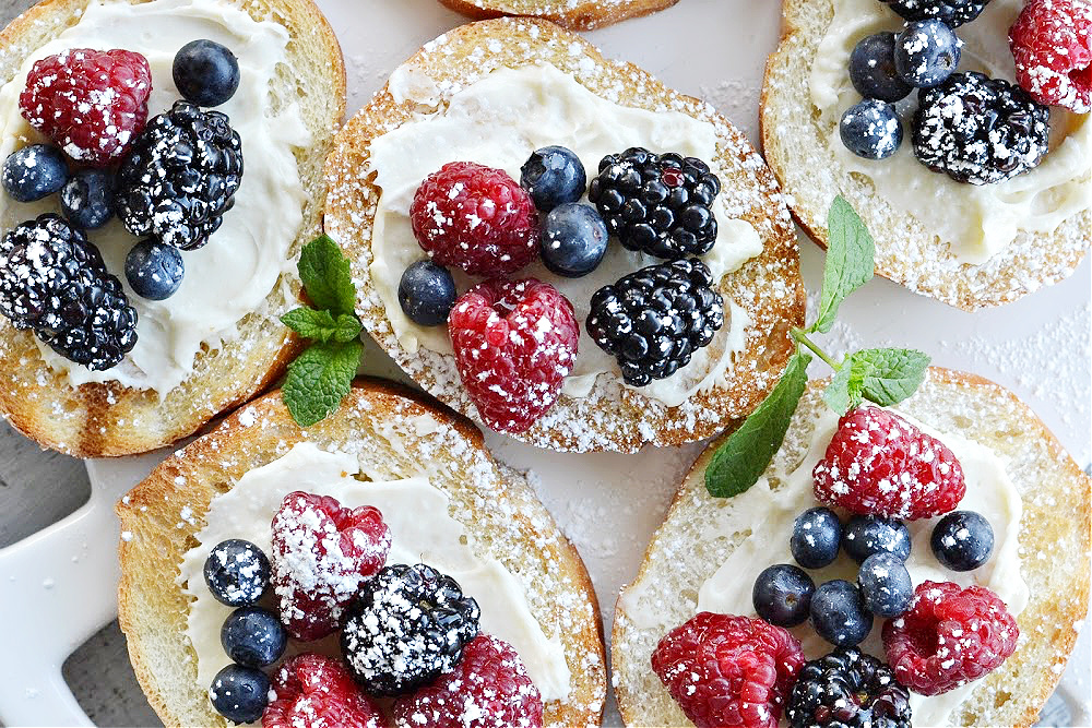 overhead and closeup of berry bruschetta- toast french bread with cream cheese spread with blueberries, blackberries and raspberries
