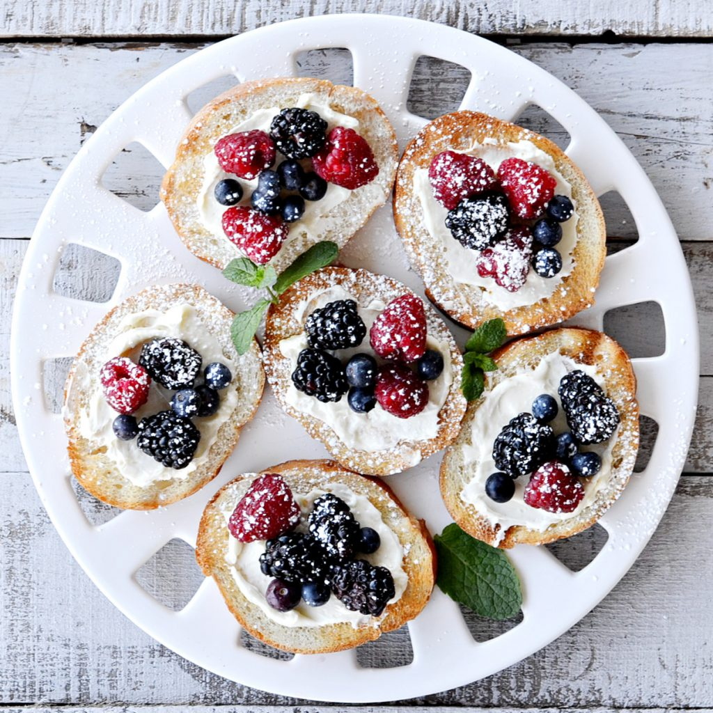 overhead view of berry bruschetta on round white platter- toast french bread with cream cheese spread with blueberries, blackberries and raspberries