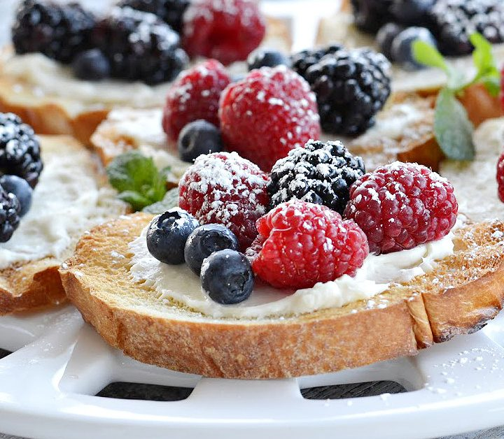 closeup view of berry bruschetta on round white platter- toast french bread with cream cheese spread with blueberries, blackberries and raspberries