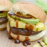 closeup of grilled slider with pineapple avocado and lots of dripping barbecue sauce