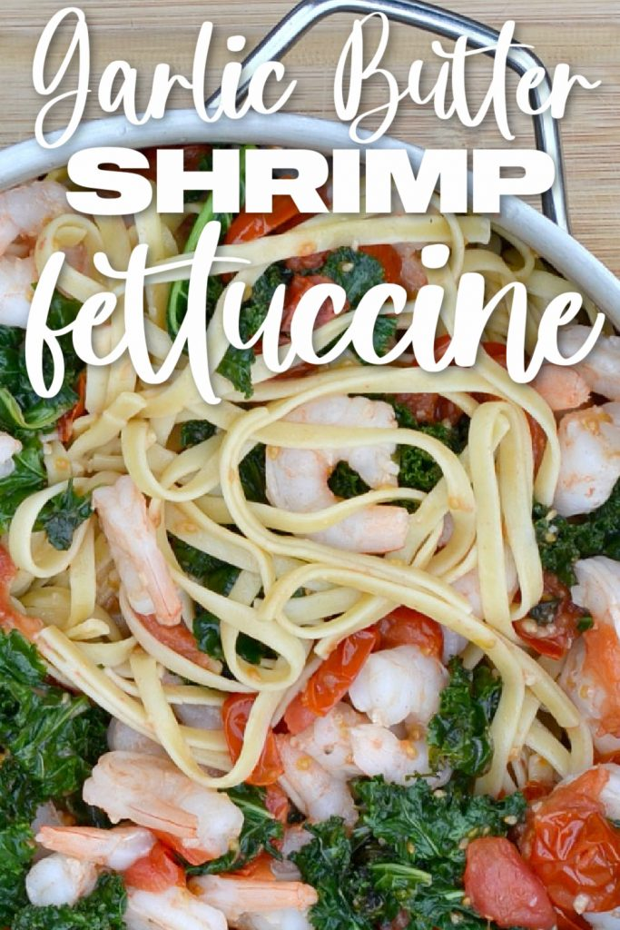overhead view of fettuccine, shrimp, cooked kale and red halved cherry tomatoes