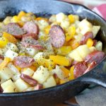 closeup view of cast iron skillet with sausage, potatoes and peppers with basil sprinkled on top