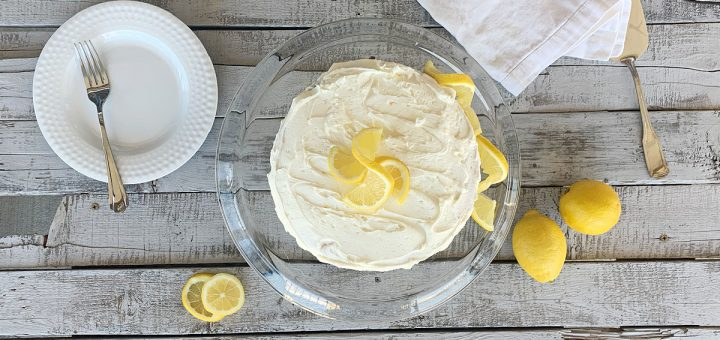 overhead view of lemon cake on clear cake stand with lemon garnish