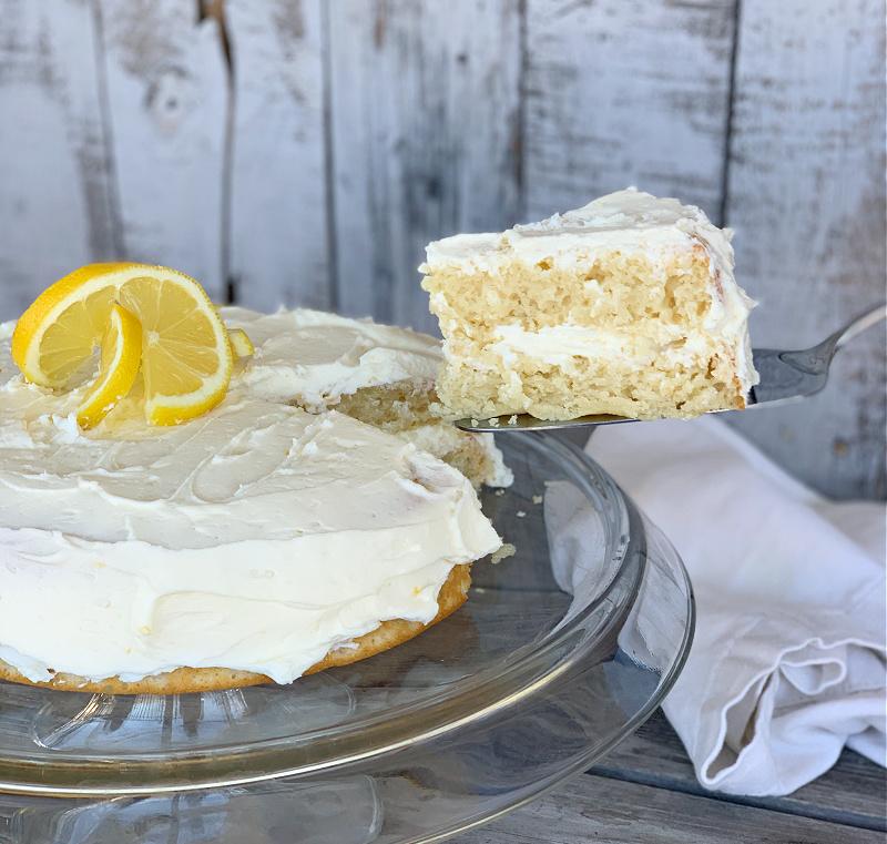 eggless lemon cake with lemon garnish on top with yummy slice on pie server