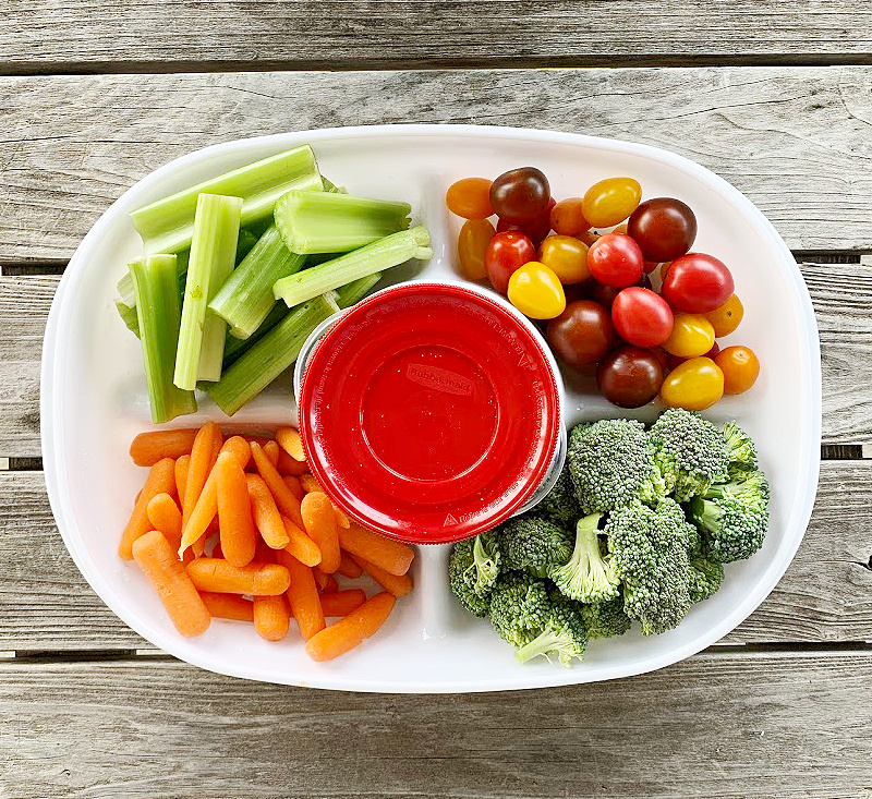 overhead view of veggie tray with celery, colorful tomatoes baby carrots and chopped broccoli