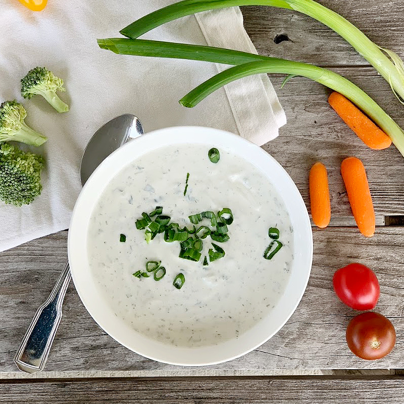 overhead view of ranch dip with scallions on top with cream napkin, green onions, carrots, cherry tomatoes, broccoli and a spoon