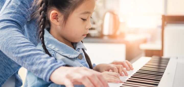 Asian young pianist teacher teaching girl kid student to play piano