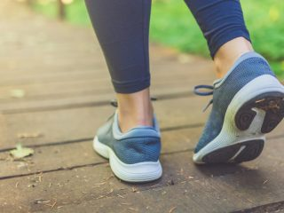 Close up of female legs with running shoes on wooden footpath in woods