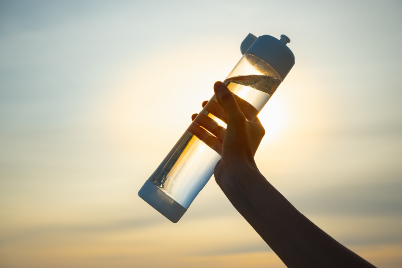 Human hand holds a water bottle against the setting sun. Close up of a reusable water bottle in a human hand