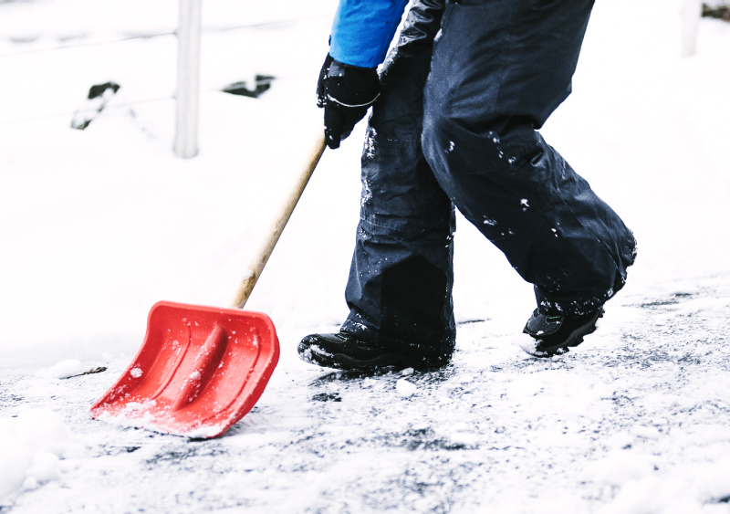 Child shovelling snow and cleaning the driveway.