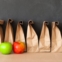 lunch bags lined against black chalkboard with one red apple and one green apple