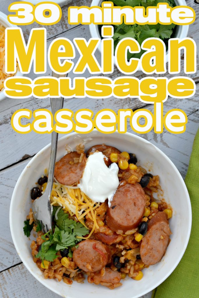 overhead view of mexican sausage casserole in white bowl with shredded cheese, sour cream and cilantro for garnish