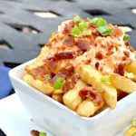 closeup of cheese fries in white bowl pile high with french fries with pimento cheese on top with crumbled bacon and green onions