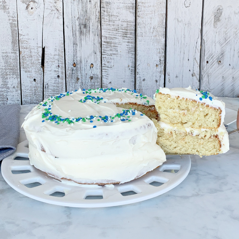 Eggless vanilla cake with green, blue and white sprinkles with pieces being taken out