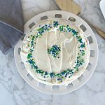 overhead view of vanilla cake on maple countertop on round cake plate. Cake has blue, green and white sprinkles