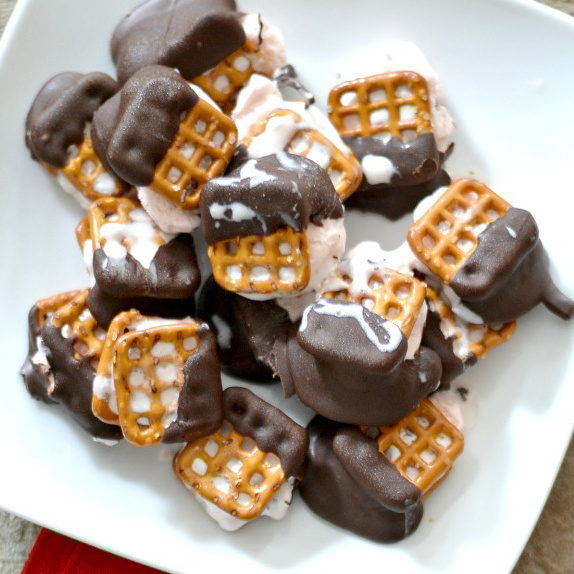 overhead ice cream bites with pretzels and dipped in chocolate on white plate with red napkin