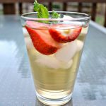 glass of green tea with ice cubes, strawberries and mint leaves